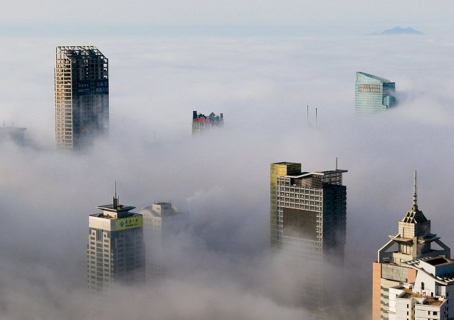 Buildings are seen among fog in Qingdao, Shandong province, China