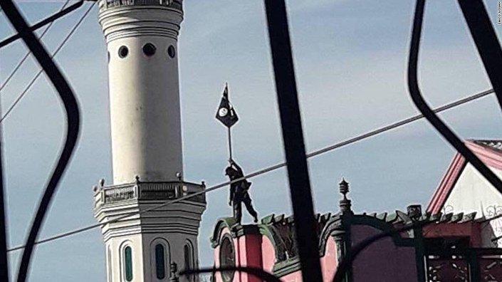 24 Mayıs'ta kaydedilen görüntülerde Maute militanının bir cami yanındaki okulun çatısına IŞİD bayrağı diktiği görülüyordu.