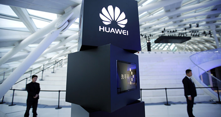 Security personnel stand near a pillar with the Huawei logo at a launch event for the Huawei MateBook in Beijing, Thursday, May 26, 2016