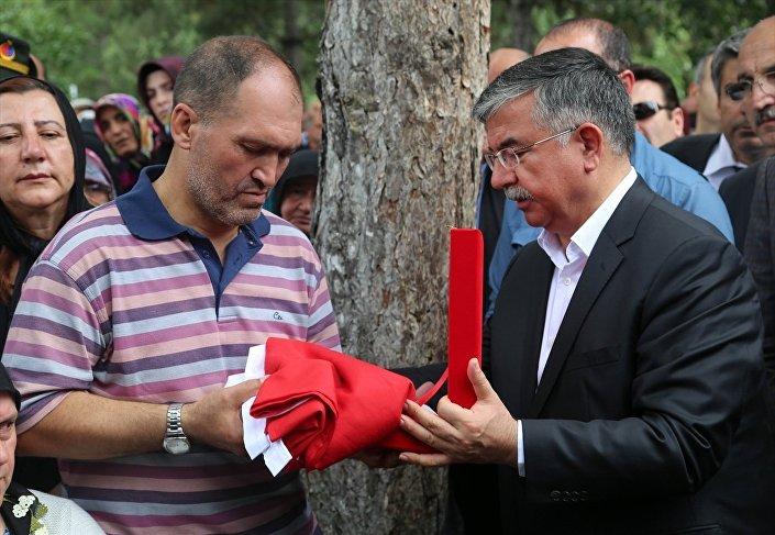 Milli Eğitim Bakanı İsmet Yılmaz, yaşamını yitiren öğretmenin babası Sadık Yalçın'a tabuta sarılan bayrağı teslim etti