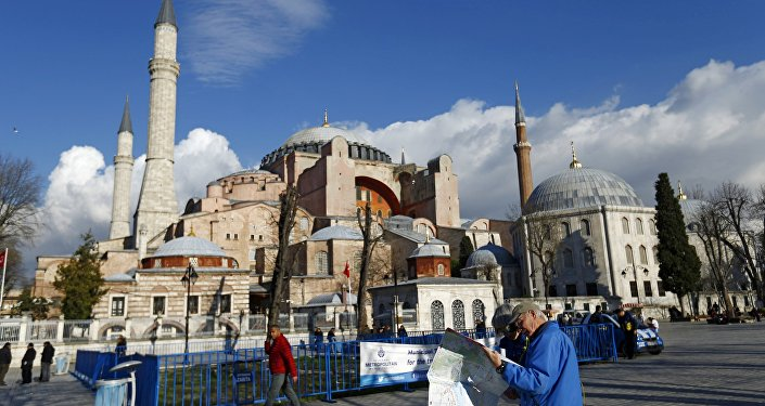 A tourist couple checks a map, near the Byzantine-era monument of Hagia Sophia, at Sultanahmet square in Istanbul,Turkey January 14, 2016