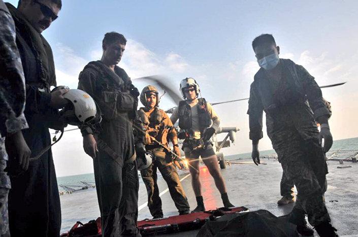 ABD Donanma askerleri USS John McCain'in kayıp personeli için yapılan arama kurtarma çalışmalarında bulunan bir cesedi donanmaya ait bir helikoptere taşıyor.