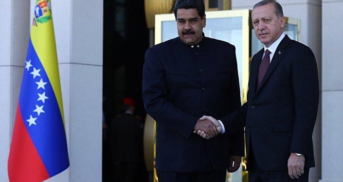 İki ülke heyetlerinin takdimi sonrasında Erdoğan ve Maduro, merdivenlerde Türkiye ve Venezüella bayrakları önünde el sıkışarak poz verdi.