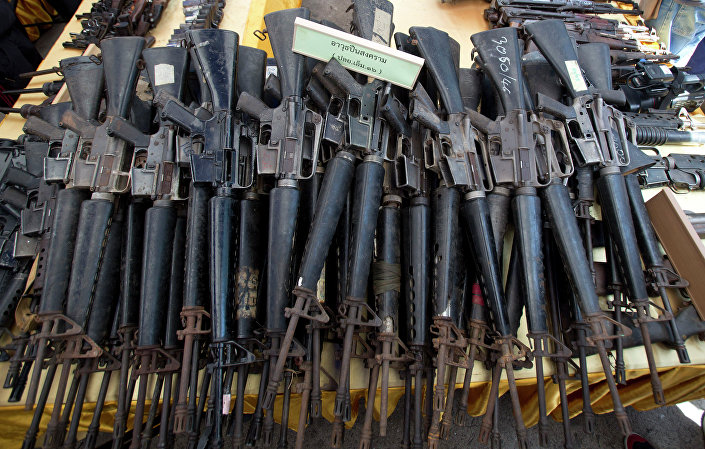 Confiscated M-16 rifles are on display on a table before destruction at Samut Prakarn province, Thailand