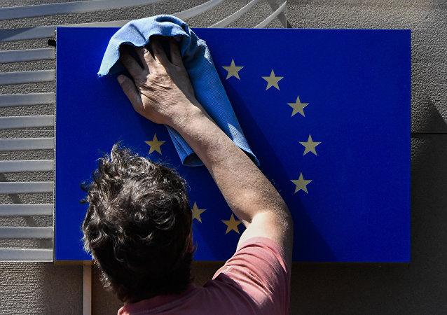 A worker wipes an EU flag clean.