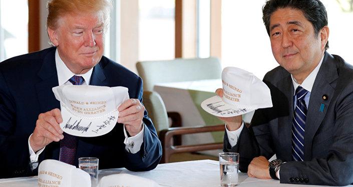 Trump ve Abe, üzerinde 'Donald & Şinzo, ittifakı daha da güçlü kılıyor' yazılı şapkaları imzaladı.