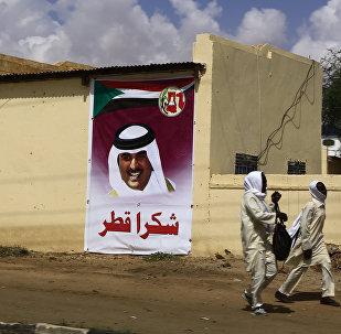 Sudan'da Katar'a teşekkür ifadeleri içeren bir afişin önünden geçen öğrenciler