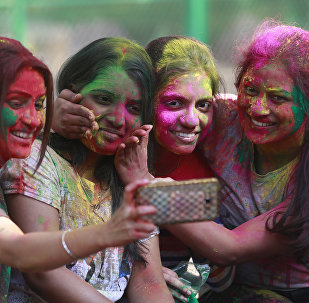 Indian girls take selfie as they celebrate Holi, the Hindu festival of colors, in Mumbai, India, Monday, March 13, 2017