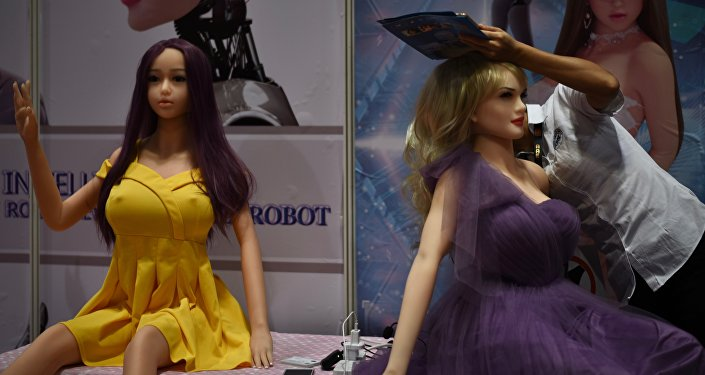 An exhibitor (R) adjusts an adult sex toy doll at her stall during the Asia Adult Expo in Hong Kong