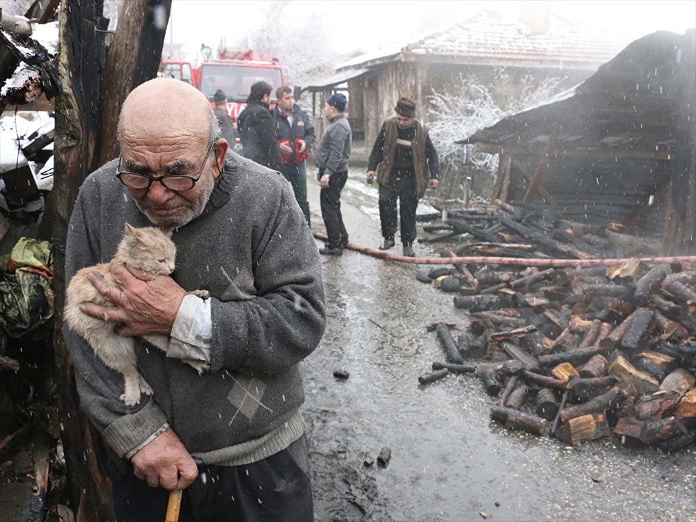 Kedisine sarılıp evinin yanışını izledi