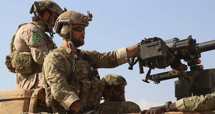 YPG simgesi taşıyan üniformalar giyen ABD askerleri.