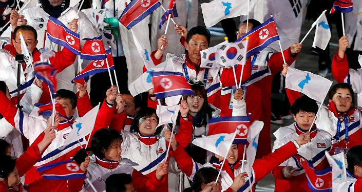 Kuzey Kore ve Güney Koreli sporcular ellerinde birleşik Kore, Kuzey Kore ve Güney Kore bayraklarıyla yine birlikte yürüdü.