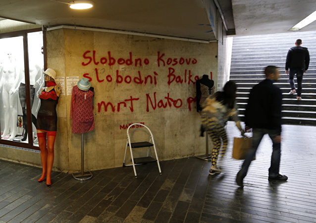 People pass through an underground passage with graffiti on the wall that reads: Free Kosovo, Free Balkan, Death for NATO, in Belgrade, Serbia (File)