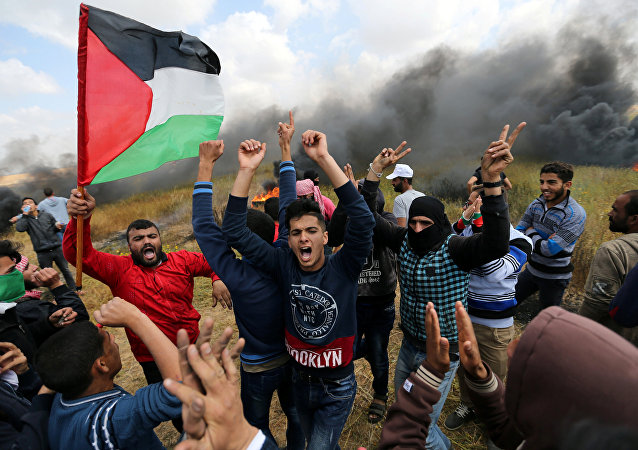 Palestinians shout during clashes with Israeli troops, during a tent city protest along the Israel border with Gaza, demanding the right to return to their homeland, the southern Gaza Strip March 30, 2018.