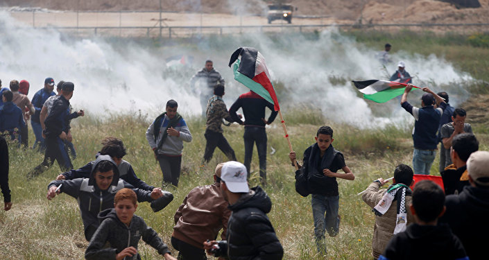 Palestinians run from tear gas fired by Israeli troops during clashes, during a tent city protest along the Israel border with Gaza, demanding the right to return to their homeland, east of Gaza