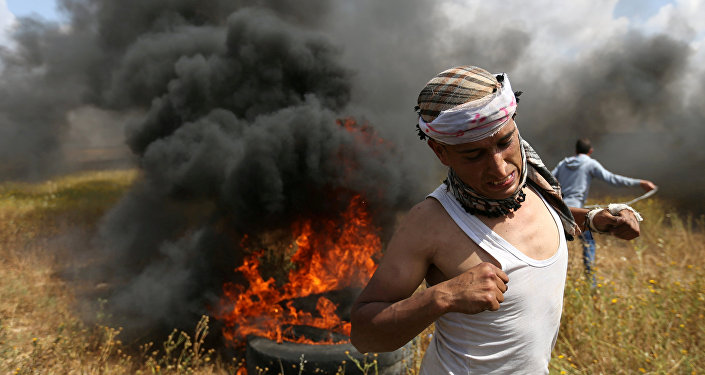 A Palestinian runs during clashes with Israeli troops, during a tent city protest along the Israel border with Gaza, demanding the right to return to their homeland, the southern Gaza Strip