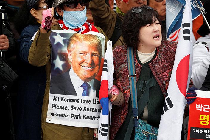 Park'ın destekçileri de üzerinde ABD Başkanı Donald Trump'ın fotoğrafının yer aldığı ve Tüm Koreliler, ABD'yi seviyor. Lütfen Kore'yi kurtar yazan pankartlar taşıdı.