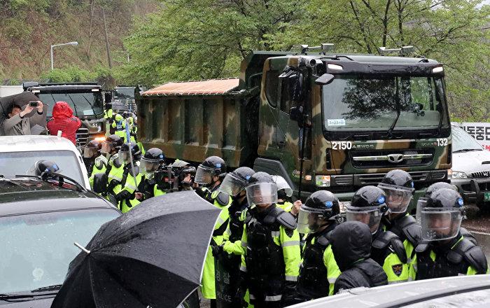 THAAD sisteminin bulunduğu üsse inşaat kamyonlarının hükümetin verdiği emir doğrultusunda gelmesi 2017 ortasından bu yana üsse açılan tek yolu kapatan Güney Koreli eylemcilerin tepkisini çekti. ABD'nin bölgeye THAAD sistemi konuşlandırmasına karşı olan eylemciler yolu kapatarak ABD ordusunun üsse yakıt, gıda ve diğer malzemelerin teminini helikopterlerle yapmasına yol açıyordu.