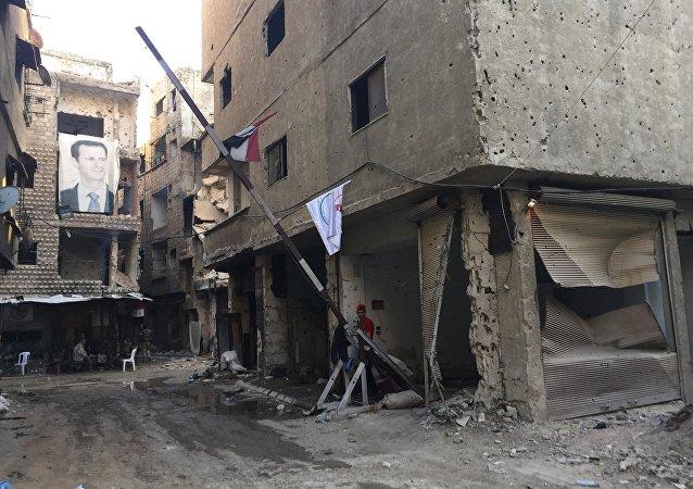 Şam'ın güneyindeki Yermuk'ta Suriye Devlet Başkanı Beşar Esad'In fotoğrafının yer aldığı afiş
