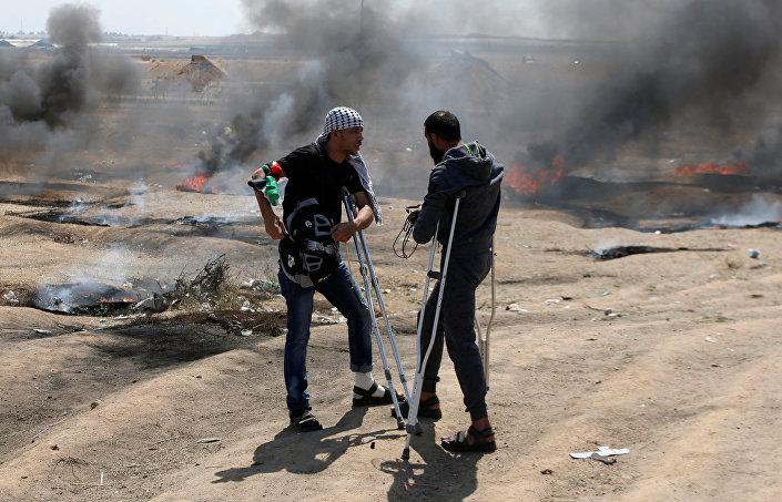 Gazze'nin İsrail sınırında 30 Mart'ta başlayan protesto dalgasının önceki eylemlerinde yaralanan Filistinliler, ABD Büyükelçiliği'nin bugün Kudüs'te açılması sebebiyle düzenlenen eylemlere koltuk değnekleriyle katıldı.