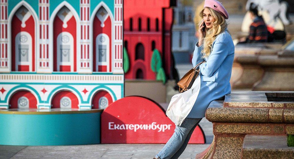 Moskova'da 2018 FIFA Dünya Kupası'na ev sahipliği yapacak kentleri gösteren panolar önünde bir Rus kadın