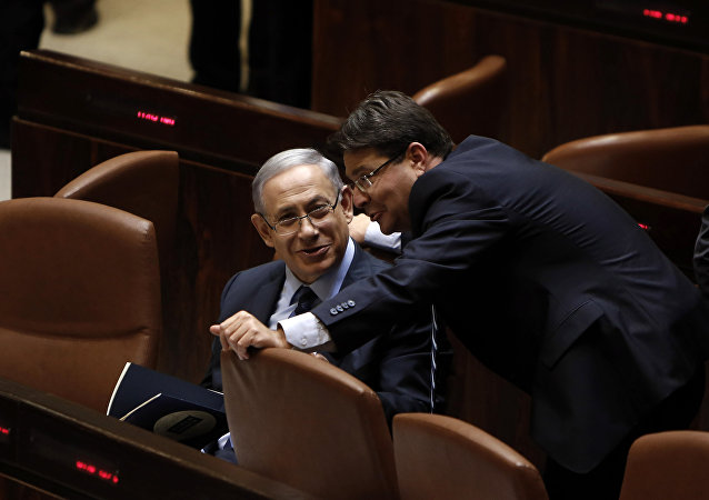 Israeli Prime Minister Benjamin Netanyahu (L) talks with  Ofir Akunis (R) during a meeting at the parliament, the Knesset, in Jerusalem, on May 13, 2015