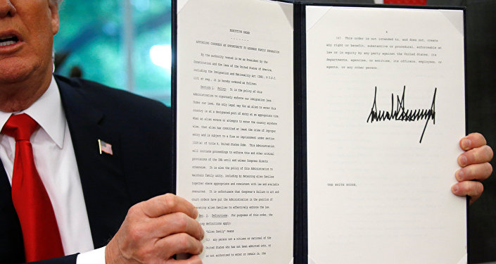 U.S. President Donald Trump displays an executive order on immigration policy after signing it in the Oval Office at the White House in Washington, U.S., June 20, 2018.