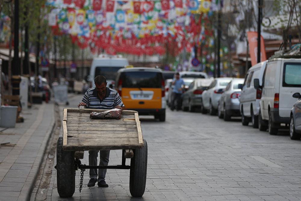 Hamallık yapan bir vatandaş çek çek arabasıyla bayrakların altından geçiyor.