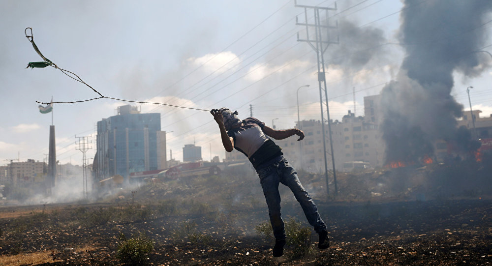 Batı Şeria'daki Ramallah kenti yakınlarında İsrail askerlerine taş atan bir Filistinli