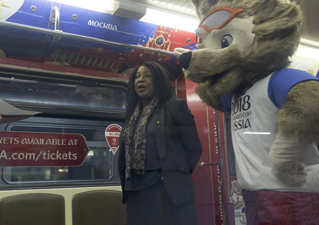 Fatma Samoura, FIFA Secretary General, left, speaks to the media with a mascot of the 2018 World Cup, the wolf named Zabivaka, seen at right, in the metro train branded for the 2018 World Cup during a ceremony in Moscow, Russia, on Tuesday, Nov. 28, 2017