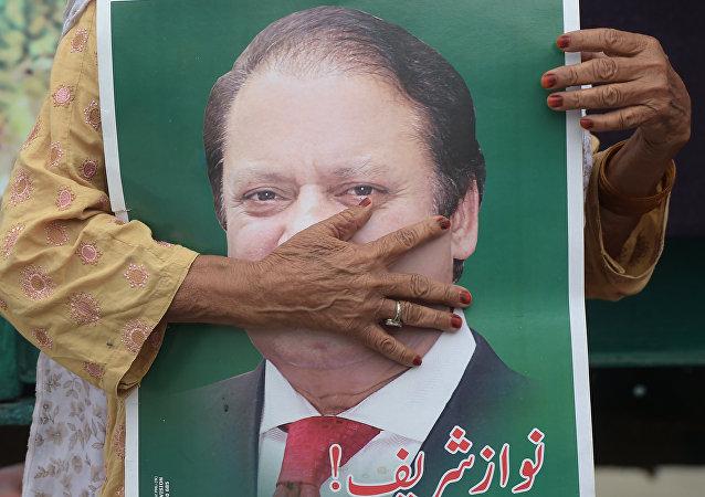 Pakistan'ın yolsuzluktan görevden alınıp hapis cezasına çarptırılan eski Başbakanı Navaz Şerif'in bir posteri ve Şerif'i Lahor'da karşılamak için bekleyen bir destekçisi