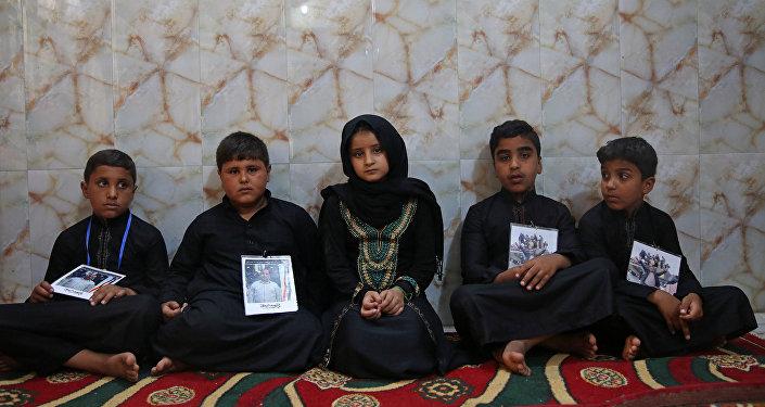 IŞİD tarafından Kerkük otoyolunda kaçırılıp öldürülen Şii erkeklerin Kerbela'daki çocukları, babalarının fotoğraflarını boyunlarına asarak güvenlik güçlerinin üstlerine düşeni yapmasını istiyor.