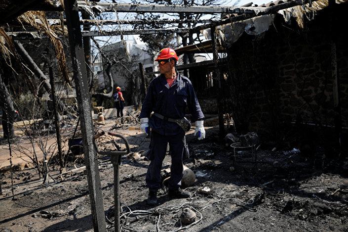 Mati köyünde yangının küle çevirdiği evlerde arama yapan bir görevli
