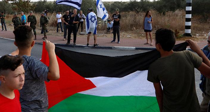 Batı Şeria'daki Rantis kontrol noktasında Tamimi'nin tahliyesini bekleyen Filistinliler, ellerinde bayraklarıyla İsraillilerle karşı karşıya.