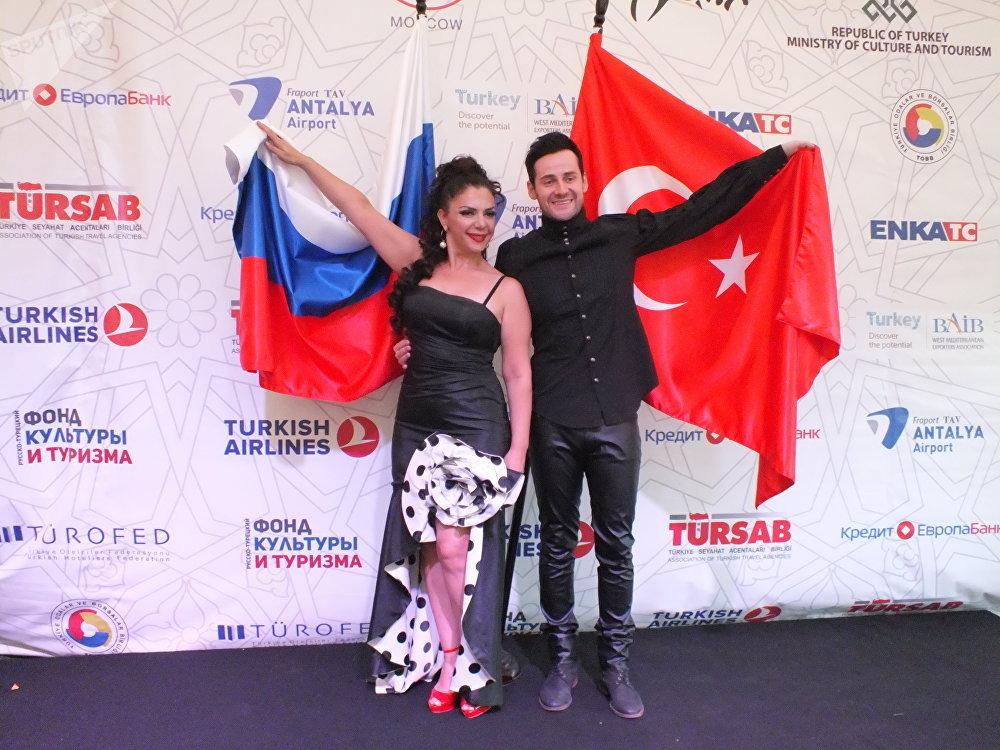 Serap Çiftçi ve Aleksandr Yelovskih Türkiye ve Rusya bayraklarıyla poz verirken.