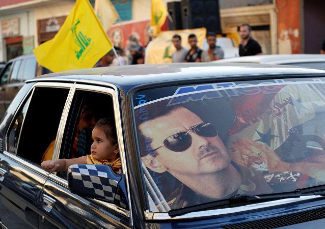 Lübnan ve Suriye'de Şiilerin cihatçılara karşı zafer kutlamalarında Hizbullah bayrakları ve Esad posterleri iç içe
