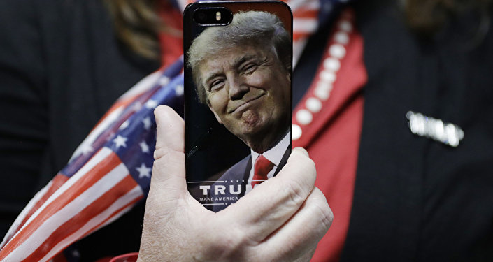 In this Thursday, Sept. 29, 2016, file photo, a woman holds up her cell phone before a rally with then presidential candidate Donald Trump in Bedford, N.H.