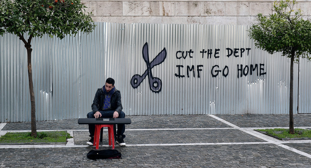 A man plays music on a digital keyboard near graffiti on a corrugated metal gate reading Cut the debt, IMF go home in Athens on February 24, 2015