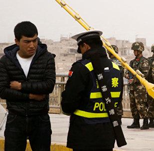 Çin'in Sincan Uygur Özerk Bölgesi'nde polis kimlik denetimi yapıyor.