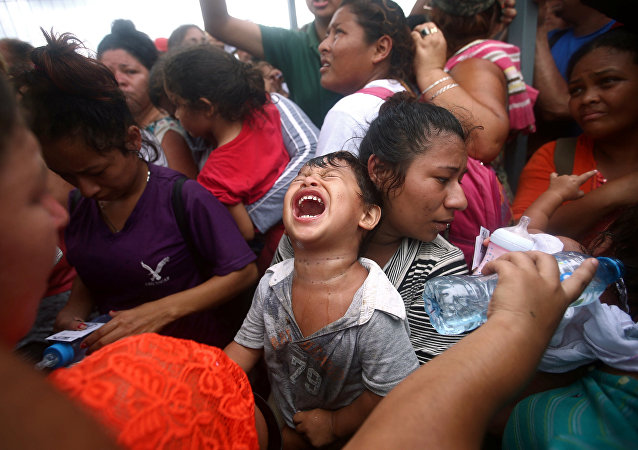 A Central American migrant child, part of a caravan trying to reach the US, cries while waiting to apply for asylum in Mexico at a checkpoint in Ciudad Hidalgo, Mexico, October 20, 2018