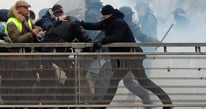 Paris'te Fransız meclisi yakınındaki köprü üzerinde polisin saldırdığı protestocuların imdadına siyah bereli ve eldivenli eki şampiyon boksör Christophe Dettinger yetişti.