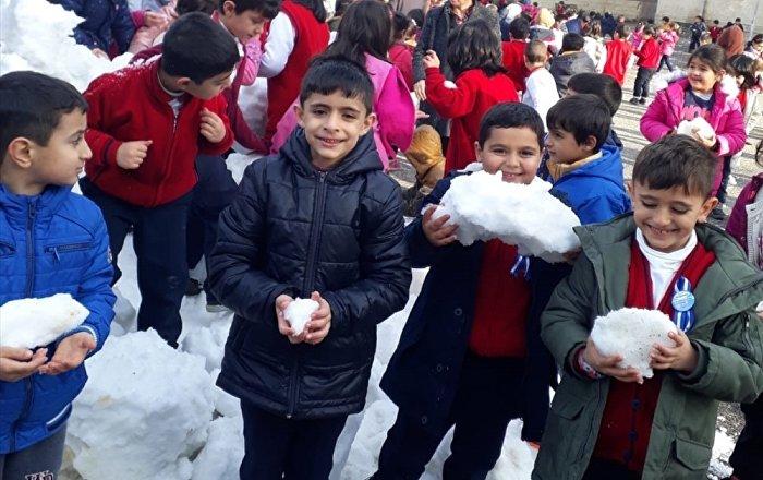 Öğrenciler kamyonla okul bahçesine taşınan karla eğlendi