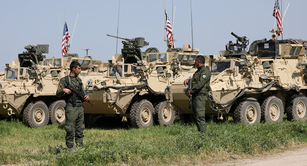 Kurdish fighters from YPG stand near U.S military vehicles in the town of Darbasiya