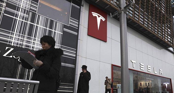 Residents walk past a Tesla store in Beijing, China, Monday, Jan. 7, 2019
