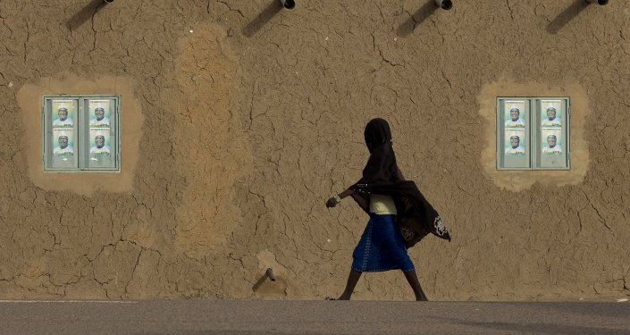 A girl walks past campaign posters on the windows of a mud brick house in Gao, Mali