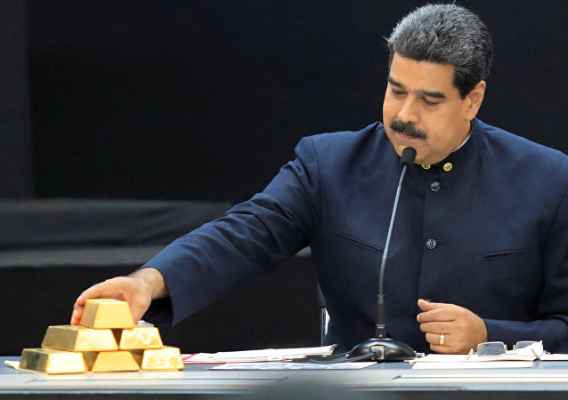Venezuela's President Nicolas Maduro touches a gold bar as he speaks during a meeting with the ministers responsible for the economic sector at Miraflores Palace in Caracas, Venezuela March 22, 2018