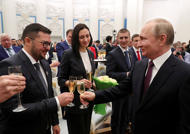 Russian President Vladimir Putin (R) toasts with participants after a ceremony to award young scientists at the Kremlin in Moscow, Russia February 7, 2019.