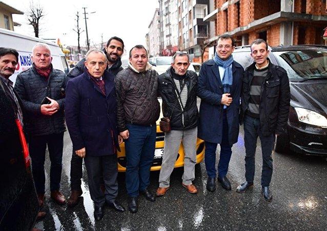 """Ticari taksi sürücüsünün sosyal medyadan yaptığı davet sonrasında taksi durağına sürpriz ziyaret gerçekleştiren CHP'nin İstanbul Büyükşehir Belediye Başkan Adayı Ekrem İmamoğlu'nun, bindiği taksinin camını açıp, """"Beni belediyeye Saraçhane'ye bırakıp gelecek"""" demesi çevredeki vatandaşları güldürdü."""