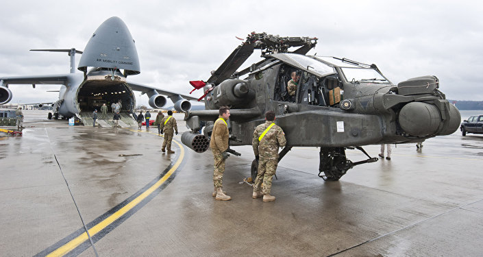 An AH-64 Apache attack helicopter stands in front of a Galaxy C-5 transport plane at the US Air Base in Ramstein, western Germany, February 22, 2017.
