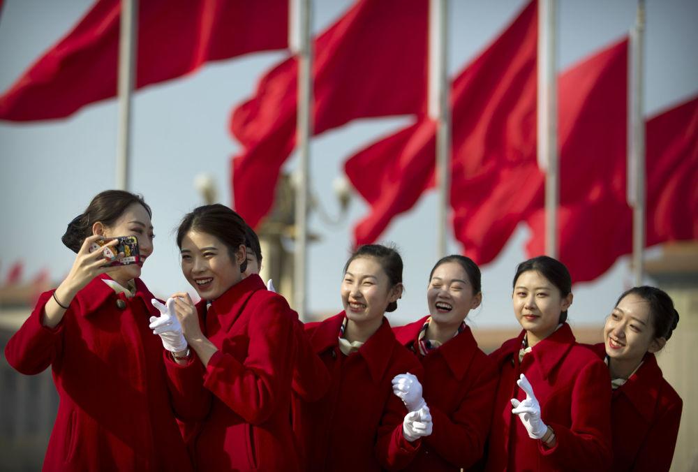 Pekin'deki Tiananmen Meydanı'nda Çin Ulusal Halk Kongresi'nin delegelerini karşılayan hostes kızları poz veriyor.